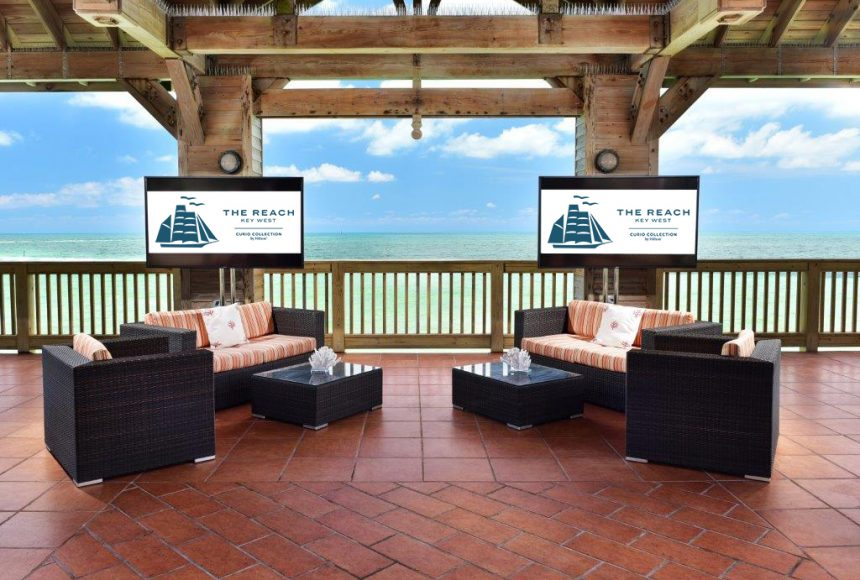 Screens behind couches in the gazebo overlooking the ocean